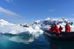 A Antártica, um selo do leopardo em um iceberg com os turistas foto de stock