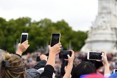 Antal av mobiltelefonkameror som lyfts för att filma och fotografera ändra av vakten arkivbild