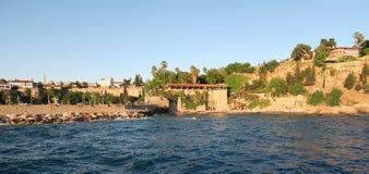 Antalya: Παραλία Mermerli και εστιατόριο με το λιμάνι, τοίχοι πόλεων στο Oldtown Kaleici, Τουρκία Στοκ Εικόνα