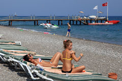 Antalya resort beach with sun loungers, berth, and sunbathers pe Royalty Free Stock Images