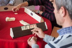 Local turkish men playing very table game Okey, or rummikub, in. Antalya,Turkey -aprill 22, 2012: Local turkish men playing very popular local table game Okey Royalty Free Stock Photography