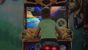 Kid having fun with racing simulator. ANTALYA, TURKEY - NOVEMBER 11, 2017: Back view of the child with model release playing motorbike space race simulator in stock video footage