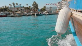 Antalya, Turkey - October 30, 2019: sea boat arriving in city port after cruise. Sailing boat board with white buoy on