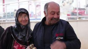 Antalya Turkiet - mars 2016: En man och en kvinna står le och omfamna, mannen som rymmer en packe av grönsallat stock video