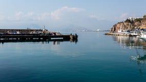 Antalya, Turquia - 22 de fevereiro de 2019: Dois pescadores que pescam perto do farol no porto na cidade velha Kaleici em Antalya imagem de stock royalty free
