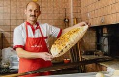 Antalyna, Turquie/le 4 août 2016 - Baker montre que le plat-pain a juste pris hors du four photo stock