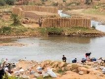 Madagascar, Antananarivo, Clay blocks at river with washing women, Stock Photo