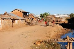 Madagascar, Antananarivo suburb with clay houses and sand road. Antananarivo suburb, clay houses, sand road with handcars, locals, children, stream and textile Stock Photo