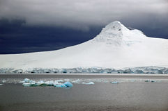 Antarctic glacial landscape. Antarctic landscape showing snow build up on a mountain and glacier regions with icebergs in the foreground stock photo