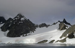 Antarctic glacial landscape. Antarctic landscape showing snow build up on a mountain and glacier regions. There is a small yacht in the foreground royalty free stock photo