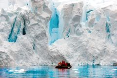 Glacier calving in Antarctic, people in Zodiac in front of escarpment of glacier stock image