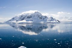 Antarctic ice-covered mountain reflected in water