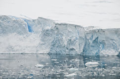 Antarctic Ice Wall. The large, fissured face of an Antarctic glacier reflects it's azure colors in the calm waterin the foreground royalty free stock photo