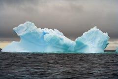 Antarctic Iceberg. Blue green Antarctic Iceberg floating royalty free stock photo