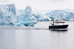Antarctic iceberg with research ship. Antarctic ice-architecture with research ship in front royalty free stock images