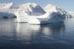 Antarctic iceberg. With snow covered mountain backdrop  - growlers and icebergs Royalty Free Stock Images