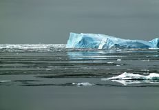 Antarctic iceberg in sunlight. One sunlit side of an Antarctic iceberg in the Southern Ocean on a nearly flat sea covered by ice floes. Picture was taken during Stock Images