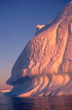 Antarctic Iceberg at Sunset. The side of a well worn iceberg lit with the warm light of sunset Royalty Free Stock Photo