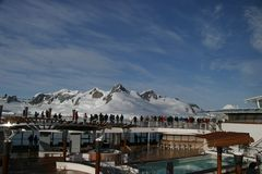 Antarctic Landscape Viewed by Cruise Passengers. Cruise ship passengers view the mountains, glaciers, icebergs, and wilderness in an Antarctic  landscape from Stock Photo