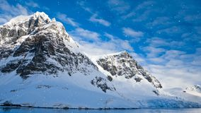 Antarctic Nature: snow-capped mountains. Antarctic Nature. Snow-capped mountains against blue cloudy sky with snow falling. Majestic winter landscape. Exploring stock video footage
