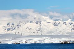 Antarctic ocean, Antarctica. Glacier Snow Covered Mountain. Dramatic blue Sky background. Wind blown clouds Royalty Free Stock Photography