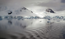 Antarctic reflection. Mountanous Antarctic landscape reflected in the icy waters with the wake of a boat across the water stock photography
