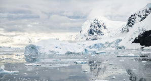 Antarctic Scenery. A typical Antarctis scene with snow-capped cliffs, calm waters and icebergs, partially lit by the suns intense rays Royalty Free Stock Image