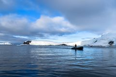 Antarctica an amazing landscape and a zodiac exploring the cold water of this enchanted place. The beauty of a glacier right over the ocean is something that royalty free stock photos