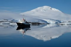 Antarctica boat ripples in a mirror blue bay beneath white snow capped mountain stock photo
