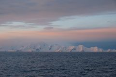 Antarctica calm pink and blue sunset over snow capped mountains. Sailing Antarctica, calm cold snow capped mountains, layers of pink and blue sunset stock photo