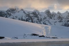 Antarctica calm pink midnight sunset over jagged mountains stock photography