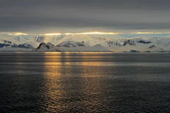Antarctica landscape, icebergs, mountains and ocean at sunrise Stock Images