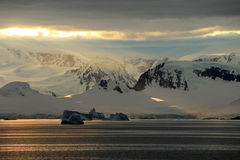 Antarctica landscape, icebergs, mountains and ocean at sunrise Royalty Free Stock Images