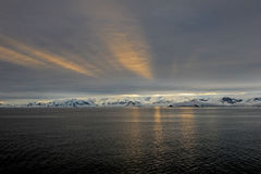 Antarctica landscape, icebergs, mountains and ocean at sunrise Stock Image