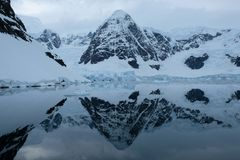 Antarctica mountains and glaciers reflect in mirror blue bay on cloudy day 3 stock photo