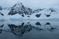 Antarctica mountains and glaciers reflect in mirror blue bay on cloudy day stock photo