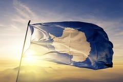 Antarctica national flag textile cloth fabric waving on the top. Sunrise mist fog royalty free illustration