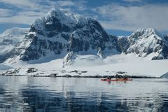 Antarctica orange and red kayaks in a mirror blue bay beneath snow capped mountains royalty free stock photo
