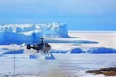Antarctica, Progress January 22, 2018: K-32C helicopter against the blue sky and iceberg carries cargo. stock images