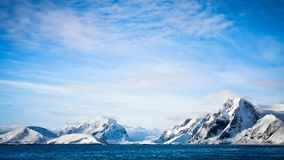 Antarctica: snow-capped mountain range against blue sky stock video footage