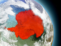 Antarctica from space. Antarctica in red on model of planet Earth with embossed countries and visible country borders. 3D illustration with clouds and reflective stock illustration