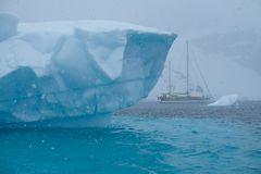 Antarctica unique jagged blue streaked iceberg with sailboat royalty free stock photography