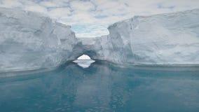 Antarktis isberg med bågen reflekterad i havet stock video