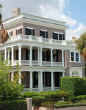 Antebellum Home Southern United States 14. A mauve stucco home with large porches and black shutters.  Surrounded by palm trees Royalty Free Stock Photo