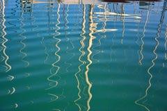 Antecedentes: reflexión en un mar de los palos del yate. Foto de archivo