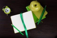 Anteckningsböcker, blyertspennor, klocka och äpple på mörk träbakgrund Royaltyfria Bilder