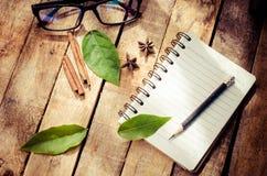 Anteckningsböcker blyertspennor, utrustning på trägolvet med morgonsolen som svagt skiner arkivfoto