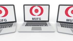Anteckningsböcker med MUFG-logo på skärmen Tolkning för ledare 3D för datateknik begreppsmässig Royaltyfri Bild