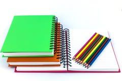 Anteckningsböcker och färgblyertspennor Royaltyfria Bilder