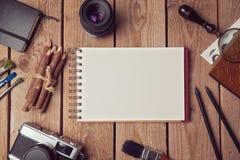 Anteckningsbokåtlöje upp för konstverk eller logodesignpresentationen med den filmkameran och linsen ovanför sikt Royaltyfri Bild